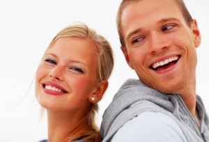 Back to back - Happy young couple smiling against a white background